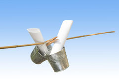 Two Galvanized Buckets Pegged On Bamboo Stick. With blue background royalty free stock images