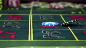 Two gambling chip falling down on roulette table, slow motion. Two standart multicolored gambling poker chips falling down on a roulette table with a lot of stock footage
