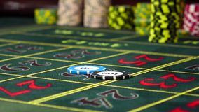 Two gambling chips falling down on roulette table, slow motion. Two different multicolored gambling chips black and blue falling down on roulette table with a stock footage