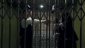 Two gangsters men in formal suits and fedora hat opening a metal forged gates. Two serious gangsters men in formal suits and fedora hat opening a metal forged stock video footage