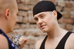 Two gangsters talking on brick wall background. Royalty Free Stock Image