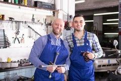 Two garage colleagues near facilities Royalty Free Stock Photos