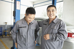 Two Garage Mechanics Laughing and Smiling at work Royalty Free Stock Photo