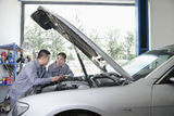 Two Garage Mechanics Working on Engine Royalty Free Stock Photo