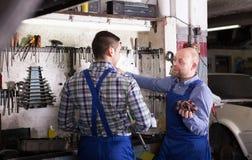 Two garage workmen near facilities Royalty Free Stock Photos