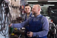 Two garage workmen near facilities Stock Photos