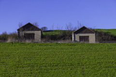 Two garages on a green hill Stock Image