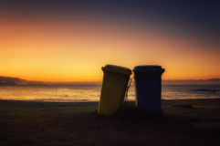Two garbage cans on beach at sunset Stock Photography
