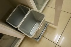 Two garbage cans of gray for separate sorting of household waste. Two grey rubber dirty trash cans filled to the top. Rain drops covering the bags stock photography