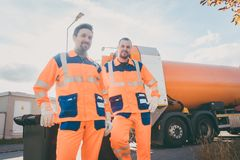 Two garbage removal service workers having short break royalty free stock photography