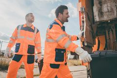 Two garbagemen working together on emptying dustbins Royalty Free Stock Image
