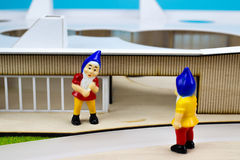 Two garden dwarfs. In front of a miniature buiding Stock Photos
