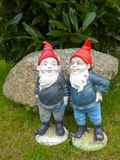 Two funny garden gnomes. Two Garden Gnomes with in front of a big stone stock photo