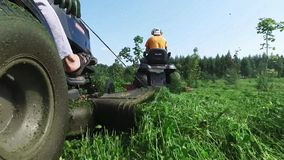 Two gardeners mow the grass on tractor. Lawn mower in the summer stock footage