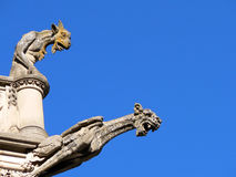 Two Gargoyles. On the roof of a European style building menacingly look down from above Stock Image