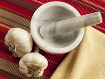 Two garlic bulbs with mortar and pestle Royalty Free Stock Photos