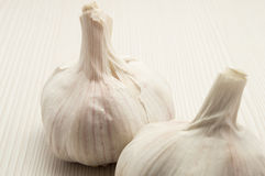 Two garlic on a wooden white table Stock Photos