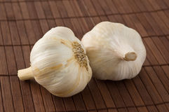 Two garlic heads on a bamboo mat. Stock Image