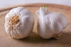 Two Garlic heads on a wood cutting board Royalty Free Stock Photography
