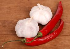 Two garlics and chilli peppers Stock Photos