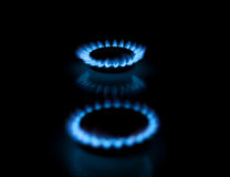 Two gas burners with flames on dark background. Two gas stove burners with blue flames. Illustration of traditional energy sources.  Shallow depth-of-field Stock Image