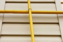 Two gas pipes over the siding wall Royalty Free Stock Photography