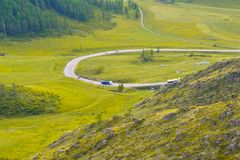 Two gasoline tank cars drive along a serpentine road in the mountains of the Altai on a bright, sunny day, below is a green fresh royalty free stock images