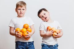 Two gay boy with oranges in the hands. On white background royalty free stock photo