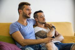 Two gay men on sofa embracing at home. Two gay men in casual outfits sitting on sofa embracing and watching TV at home Stock Photography