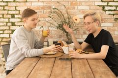 Two gay men at home in the kitchen having breakfast, sitting at the table against each other royalty free stock photography
