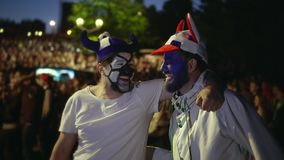 Two gay watching football. Lgbt among us. Tolerance and love 2 guys. Men soccer. Soccer fan are gay with paint face hugging playfully watching match. People from stock footage