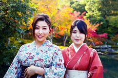 Two geishas in a zen garden in Kyoto royalty free stock image