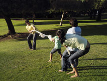Two generation family playing tug-of-war on grass in park Stock Photography