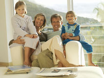 Two generation family relaxing in armchair beside balcony sliding doors, smiling, portrait royalty free stock image