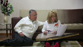 Two generation family singing. Mother playing qanun, turkish string instrument, father and son listens stock footage