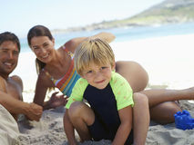 Two generation family sitting on beach, smiling, boy (5-7) crouching in foreground, portrait Royalty Free Stock Photos