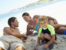 Two generation family sitting on beach, smiling, boy (5-7) crouching in foreground, portrait (tilt) Royalty Free Stock Photo