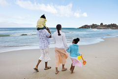 Two generation family walking along sandy beach, girl (5-7) on father's shoulders, rear view Royalty Free Stock Image