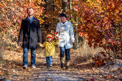 Two Generation Family Walking in Autumnal Forest Front View. Two Generation Family Walking in Colorful Autumnal Forest Alley Smiling Father Mother Holding Hands Stock Photography