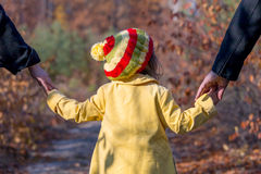 Two Generation Family Walking in Autumnal Forest Rear View. Two Generation Family Walking in Autumnal Forest Father Mother Holding Hands of Little Baby Girl Royalty Free Stock Photo
