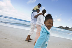 Two generation family walking on sandy beach, girl (7-9) smiling, side view, portrait (tilt) Stock Image