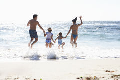 Two generation family wearing swimwear, jumping above surf on sandy beach, side by side, holding hands, rear view, sunlight shimme. Ring on sea Stock Photos