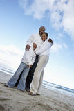 Two generation family in white clothing embracing on beach, smiling, portrait, low angle view (tilt) Royalty Free Stock Image