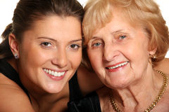 Two generations. A portrait of a granddaughter hugging her grandma over white background Stock Image