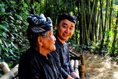 Two generations from two different cultures. A senior with traditional local headdress and younger persons are interacting nicely under bamboo forest in a Stock Photos