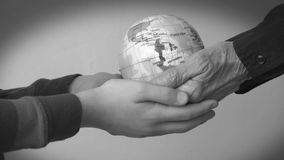 Two generations holding a globe, environmental concept. Wrinkled hands of an elder woman and young hands of a child both holding a globe of planet earth stock footage