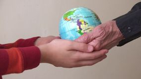 Two generations holding a globe, environmental concept. Wrinkled hands of an elder woman and young hands of a child both holding a globe of planet earth stock video