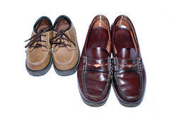 Two Generations of Shoes. A man sized pair of shoes next to shoes for a little boy Royalty Free Stock Photos