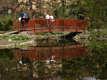 Two generations on small bridge. Young and senior couple on small garden bridge Royalty Free Stock Images