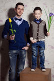 Two gentlemen: young father and his little cute son. man is hold. Two gentlemen: young father and his little cute son. men is holding yellow tulip. blue-eyed boy Royalty Free Stock Photos